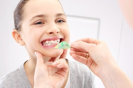 Orthodontist v's Dentist - Happy child undergoing orthodontic dental treatment- braces